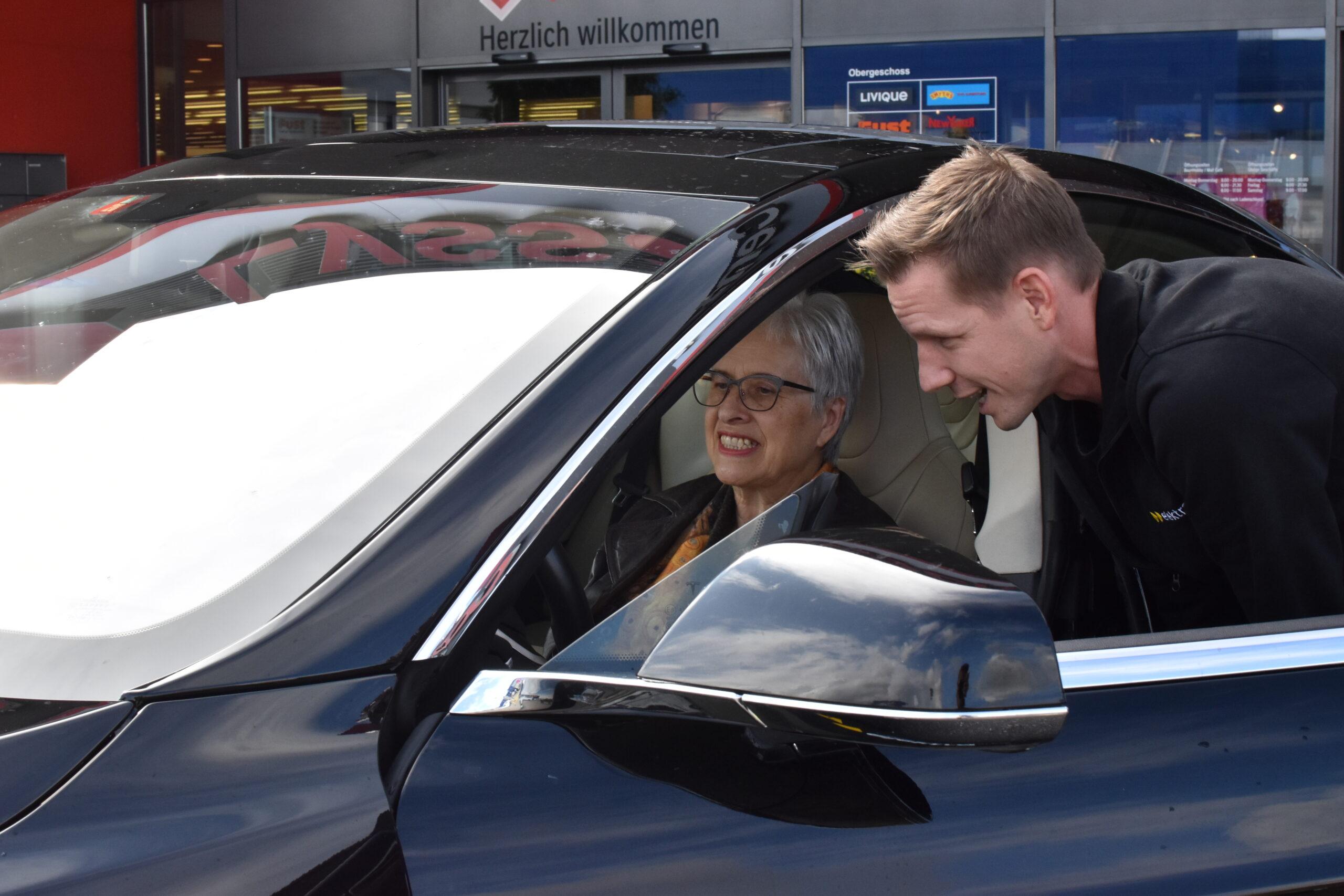 Matthias Ostermeier, Fachspezialist für Energielösungen bei Elektra, erklärt der glücklichen Wettbewerbsgewinnerin Frau Schori, wie der Tesla zu bedienen ist.