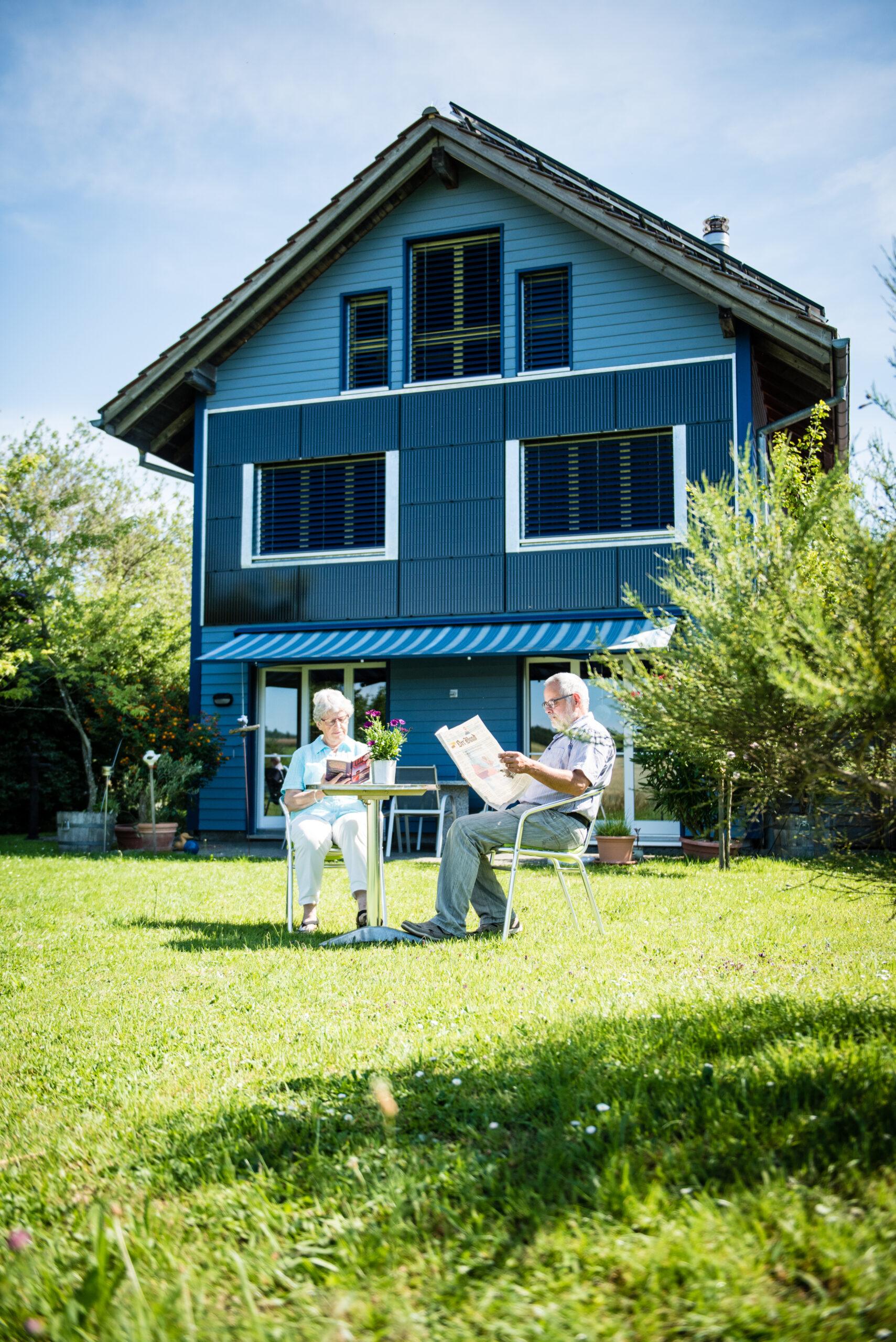Ehepaar Rubin sitzen vor ihrem Blue House, das sowohl auf dem Dach wie auch an der Fassade eine PV-Anlage hat