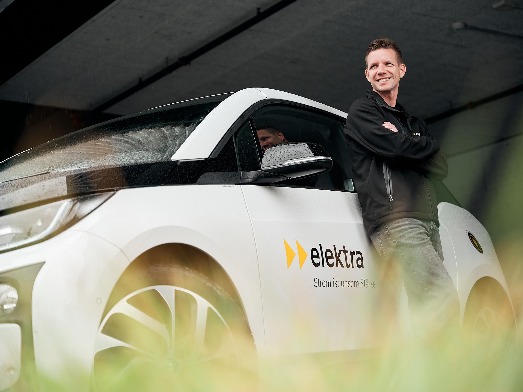 Matthias Ostermeier, Fachspezialist für Elektromobilität bei Elektra, posiert vor einem BMW i3.