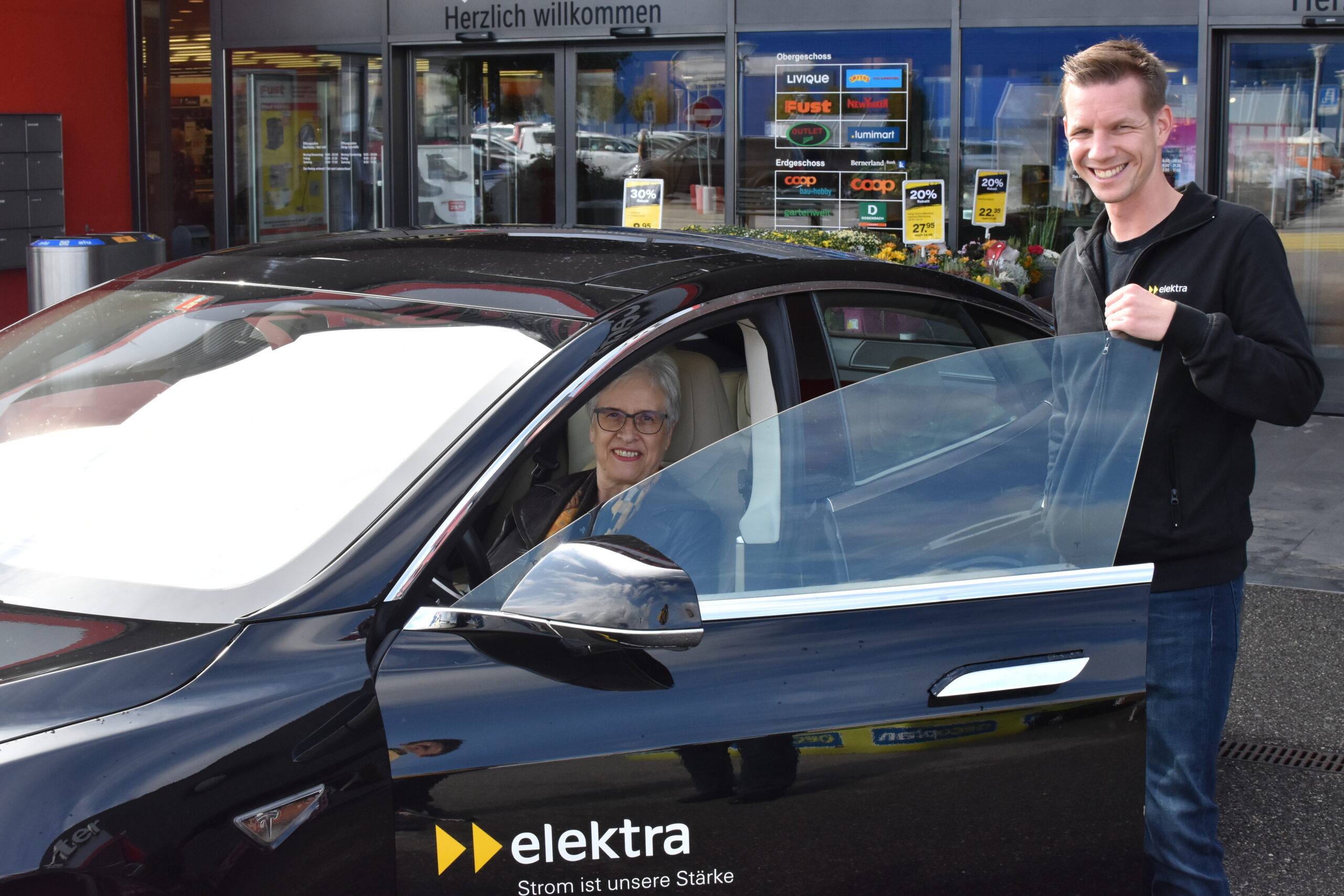 Die glückliche Gewinnerin der Mobility Week 2020 sitzt im Tesla und strahlt um die Wette mit dem Fachspezialisten für Energielösungen, Matthias Ostermeier.