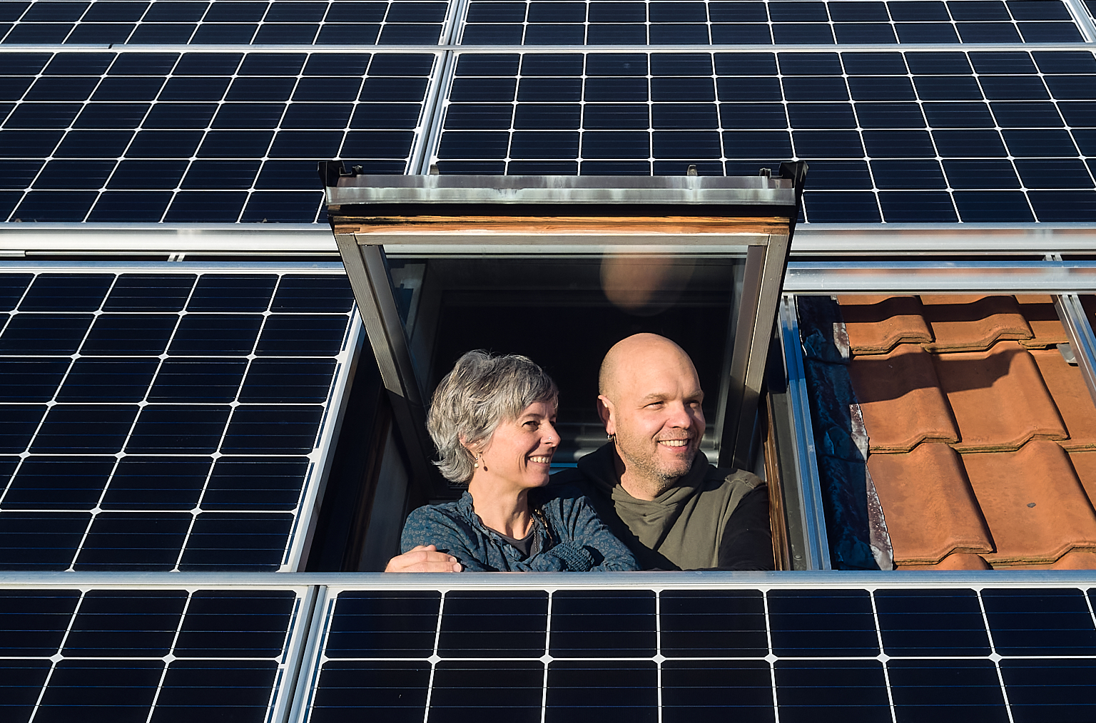 Isabelle und Lukas Loosli blicken aus dem Dachfenster, rund um sie sieht man die Panels der Solaranlage.