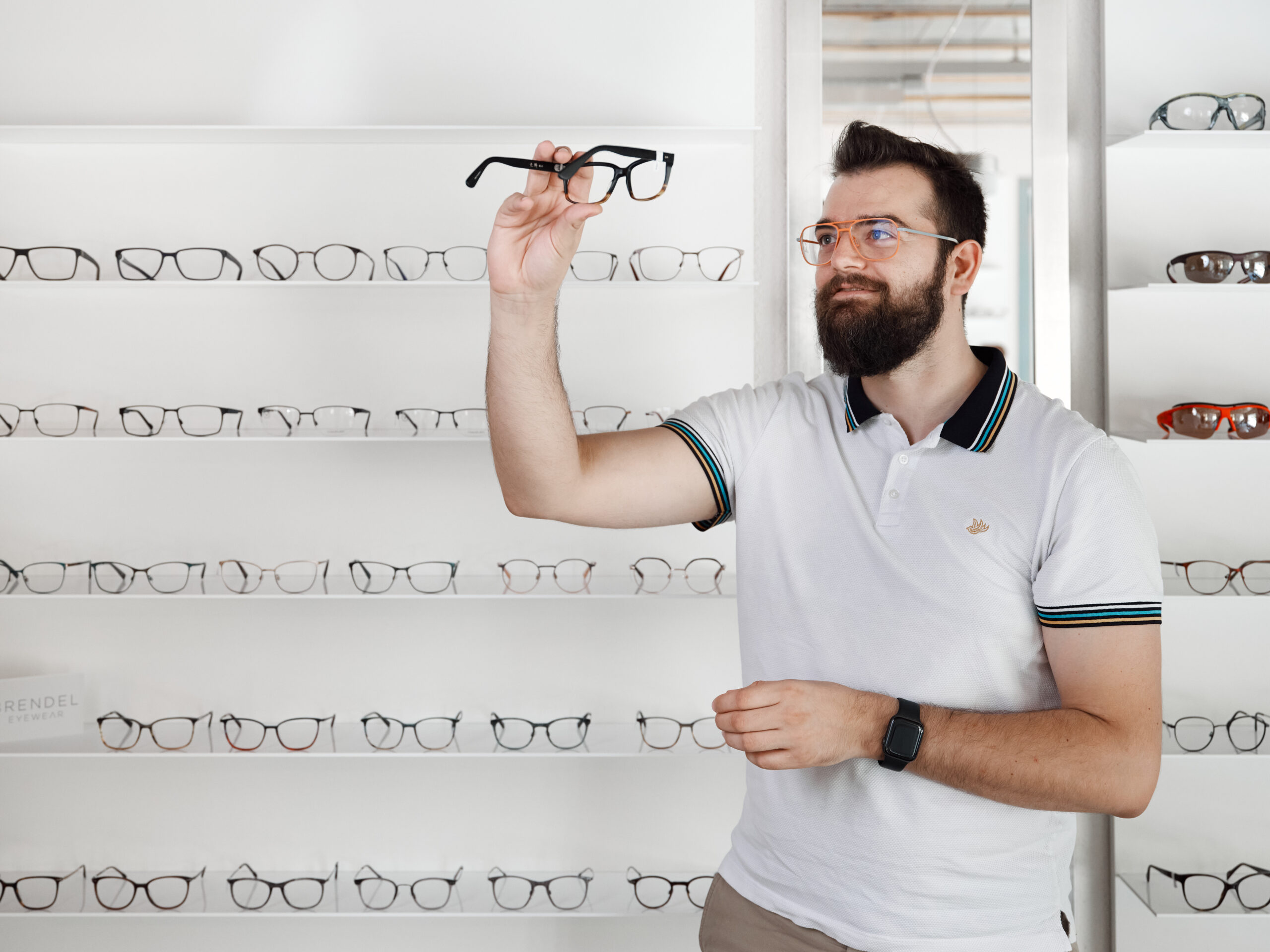 Simon Schärer, Inhaber des Brillenwerks , schaut sich eine Brillenfassung an