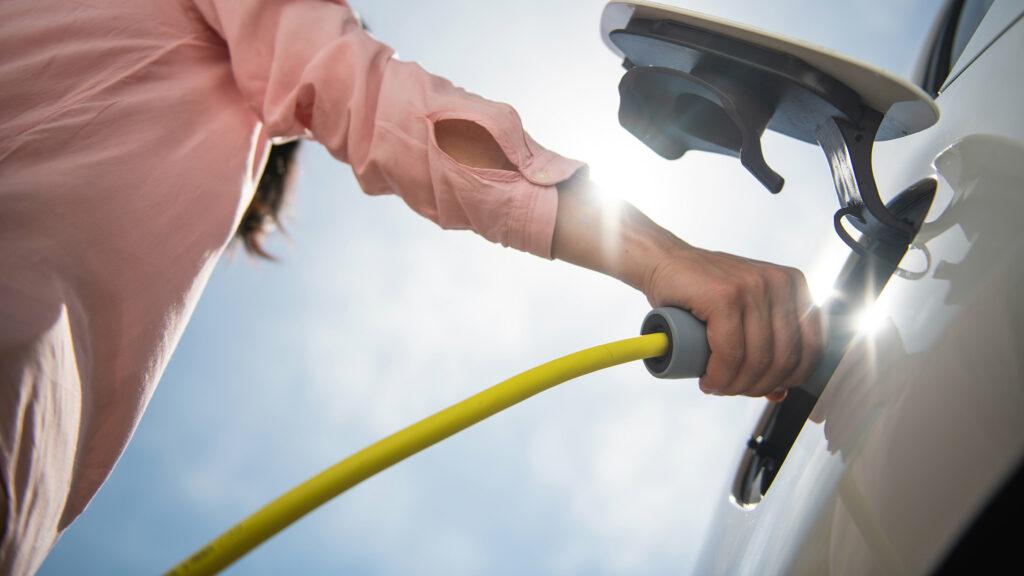 Ein Mann lädt ein Elektroauto auf.