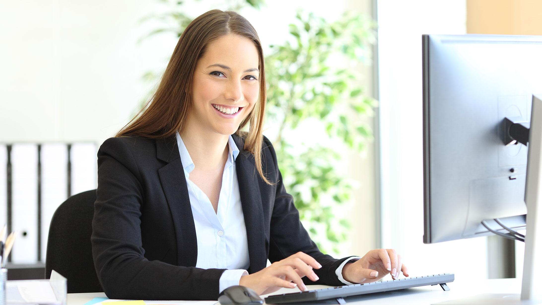 Eine laechelnde Frau vor einem Computer.