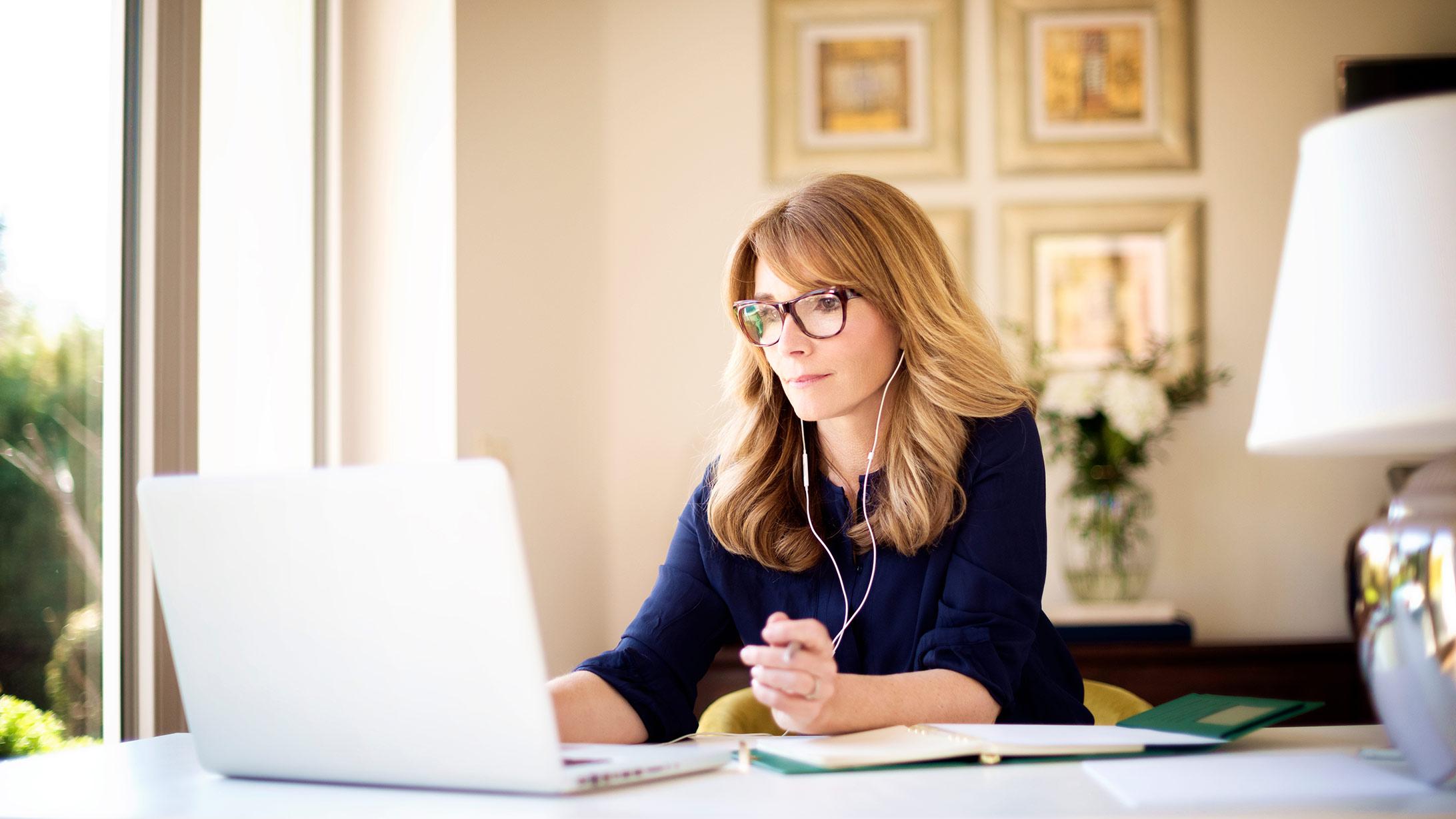 Frau sitz an einem Schreibtisch und schaut auf einen Laptop.