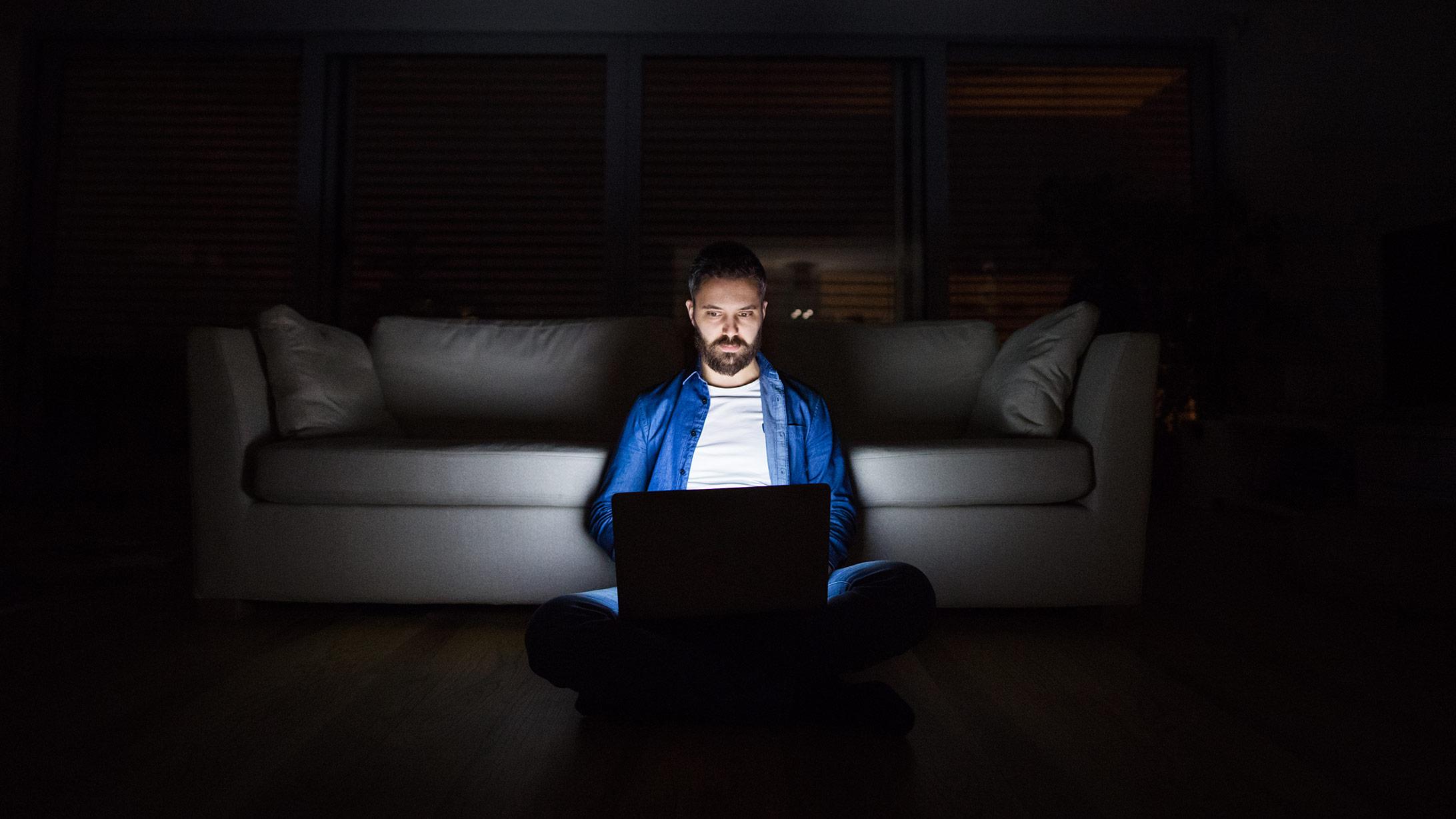 ein mann sitzt im dunkeln, sein laptopt ist die einzige lichtquelle