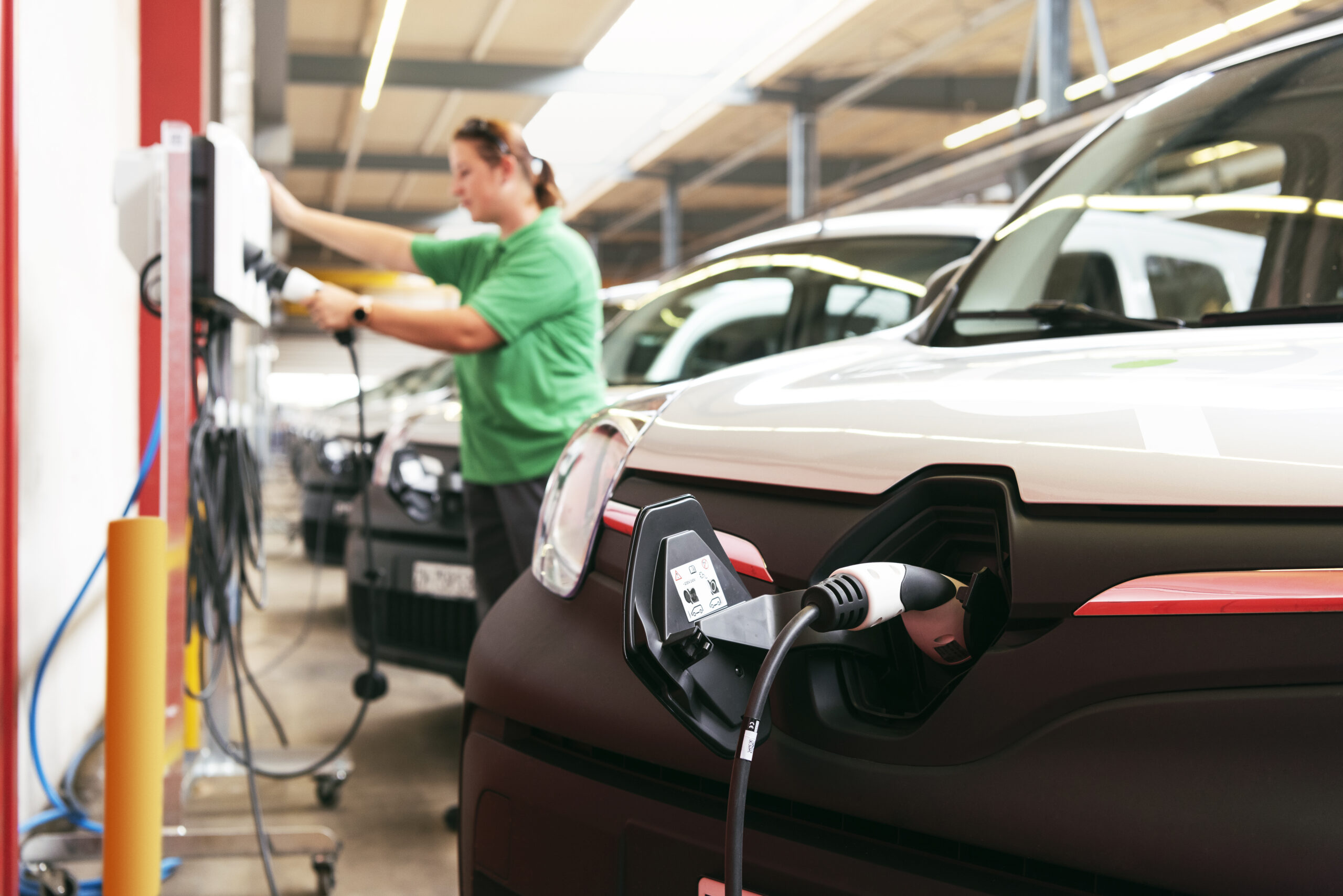 Eine Mitarbeiterin von Quickpac bedient eine Ladestation. Das Laden der Lieferwagen mittels Typ-2-Kabel ist ein Kinderspiel.