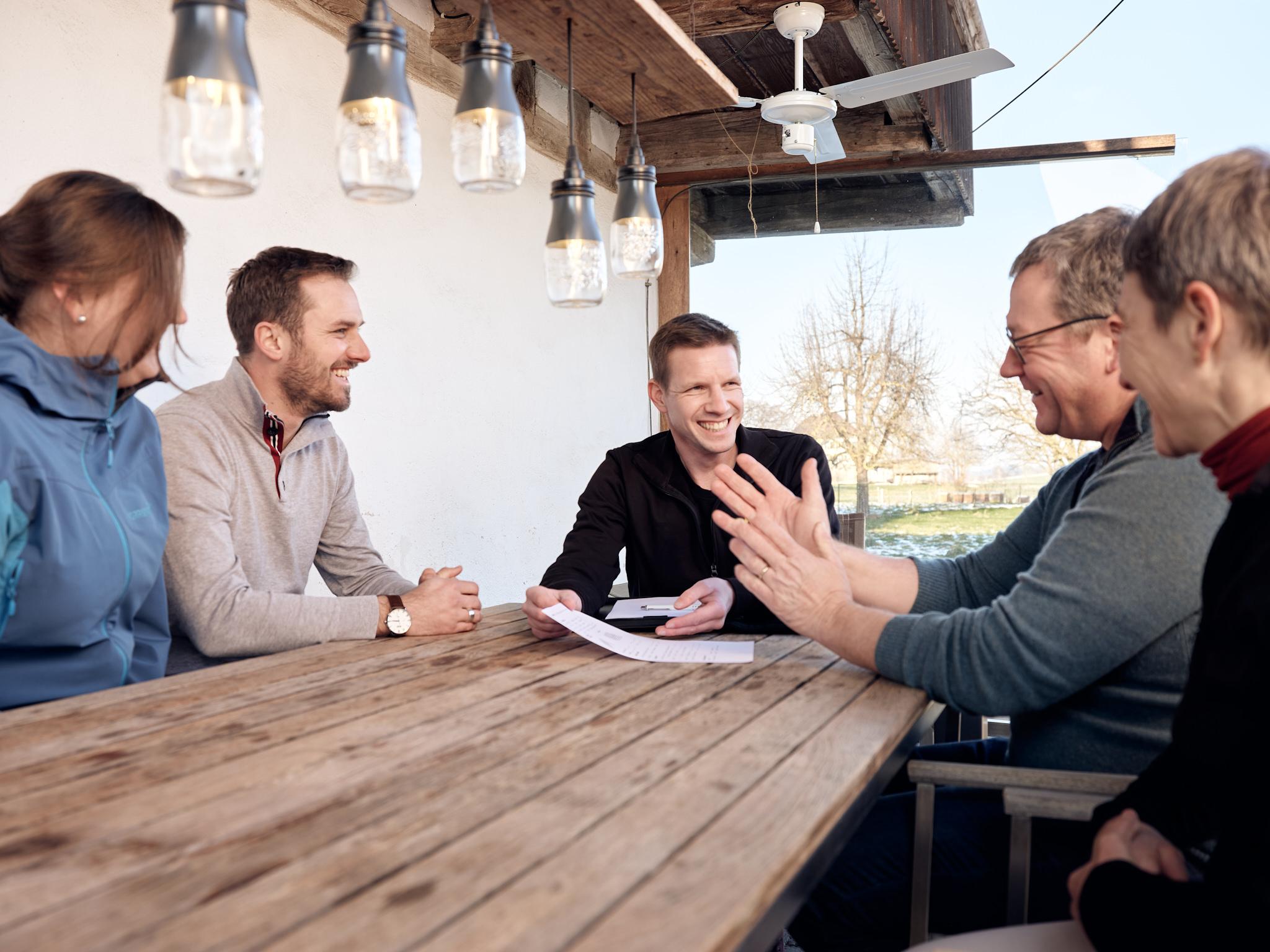 Alle - die Mieter, der Vermieter und der Spezialist für Ladelösung - sitzen am Tisch und beraten sich