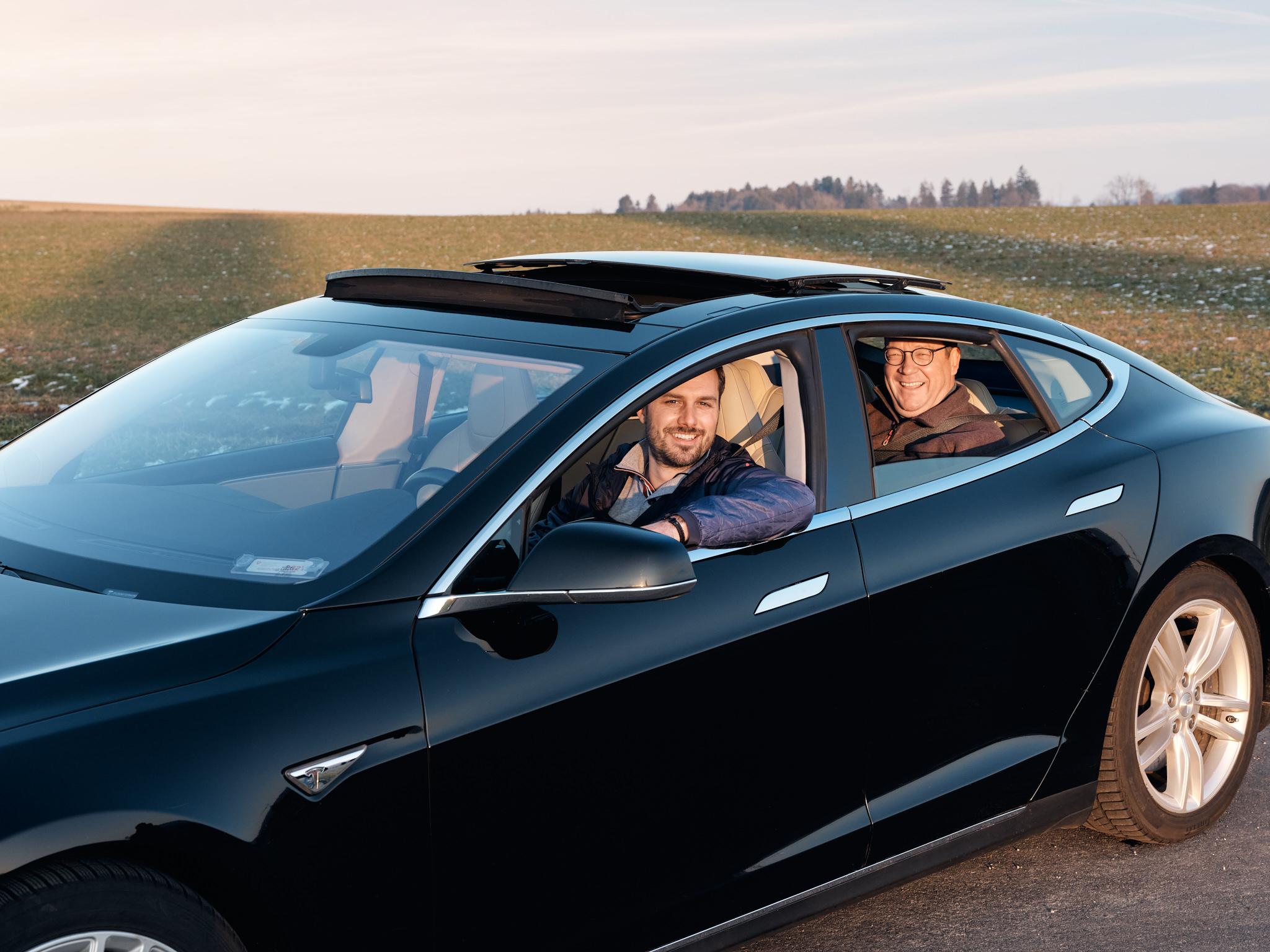 Mieter Fabian Mende und sein Vermieter Christian Huber sitzen zufrieden im Elektroauto