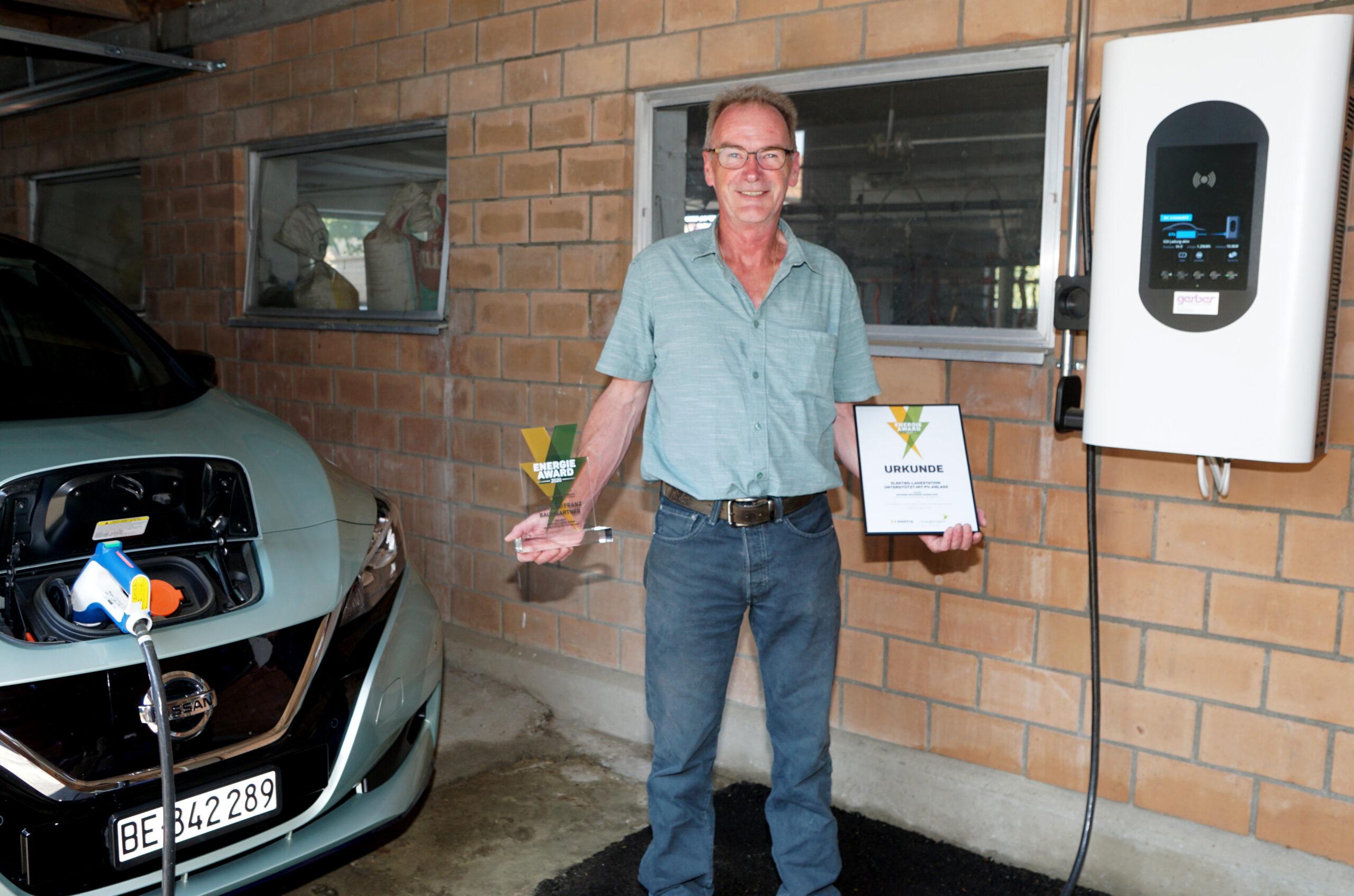Franz Baumgartner aus Moosseedorf steht zwischen Ladestation und Elektroauto, mit Pokal und Urkunde in den Händen