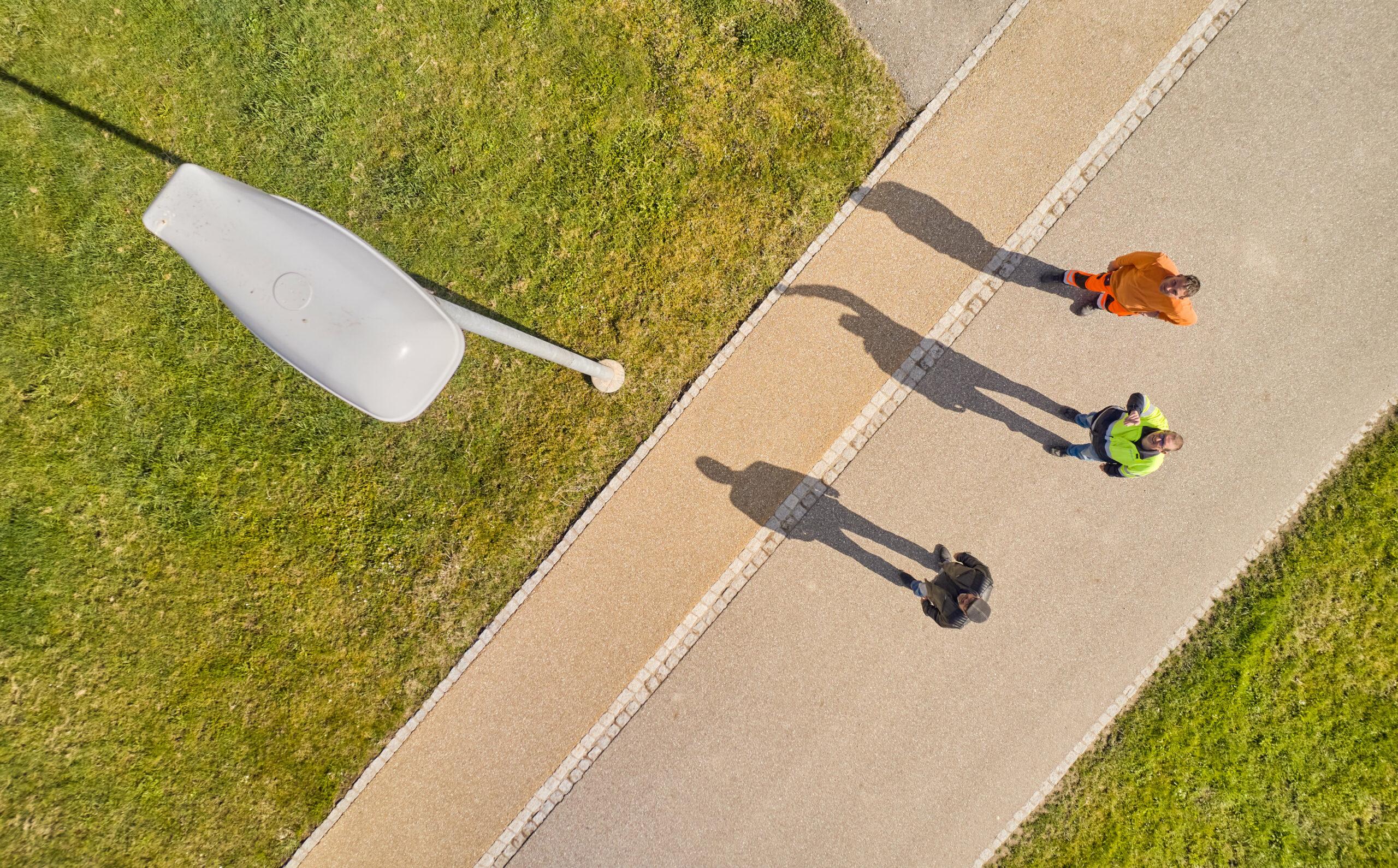Drohnenaufnahme einer Strassenlampe; unten auf der Strasse stehen die Herren Müller, Projektleiter der Elektra, Bürgi und Flückiger
