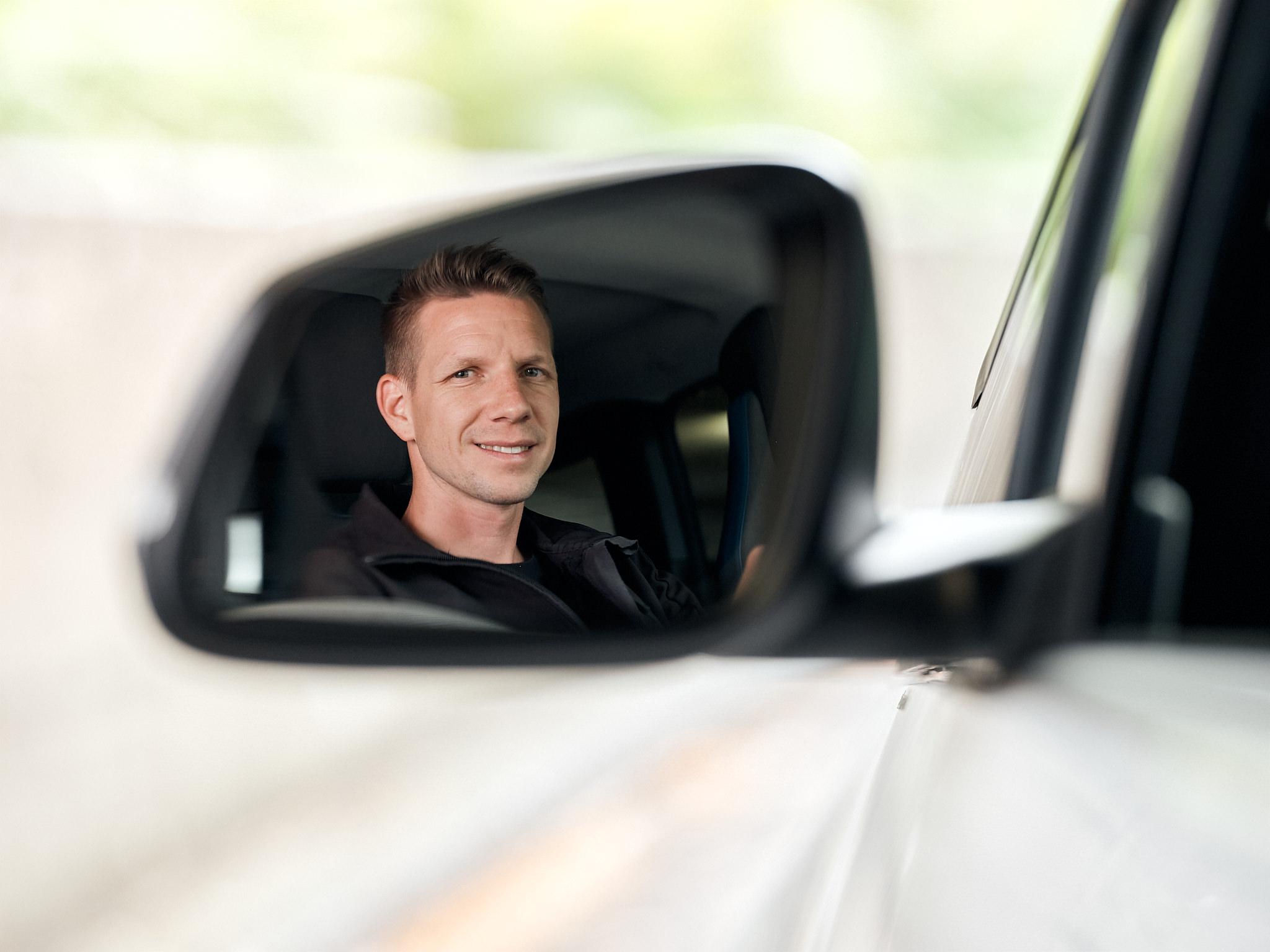 Spiegelung Matthias Ostermeier im Rückspiegel eines Elektroautos