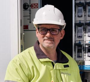 Michael Müller, Projektleiter Verteilnetz, steht vor einem Verteilkasten und blickt ernst