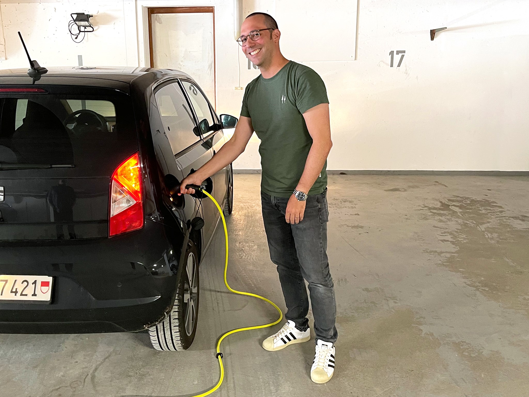 Georg Kundert steht stolz neben seinem Elektroauto und schliesst dieses an seine neue Ladestation an. Auf seine Initiative hin, hat die Überbauung in Lohn-Ammannsegg die Tiefgarage mit Ladestationen ausgerüstet.