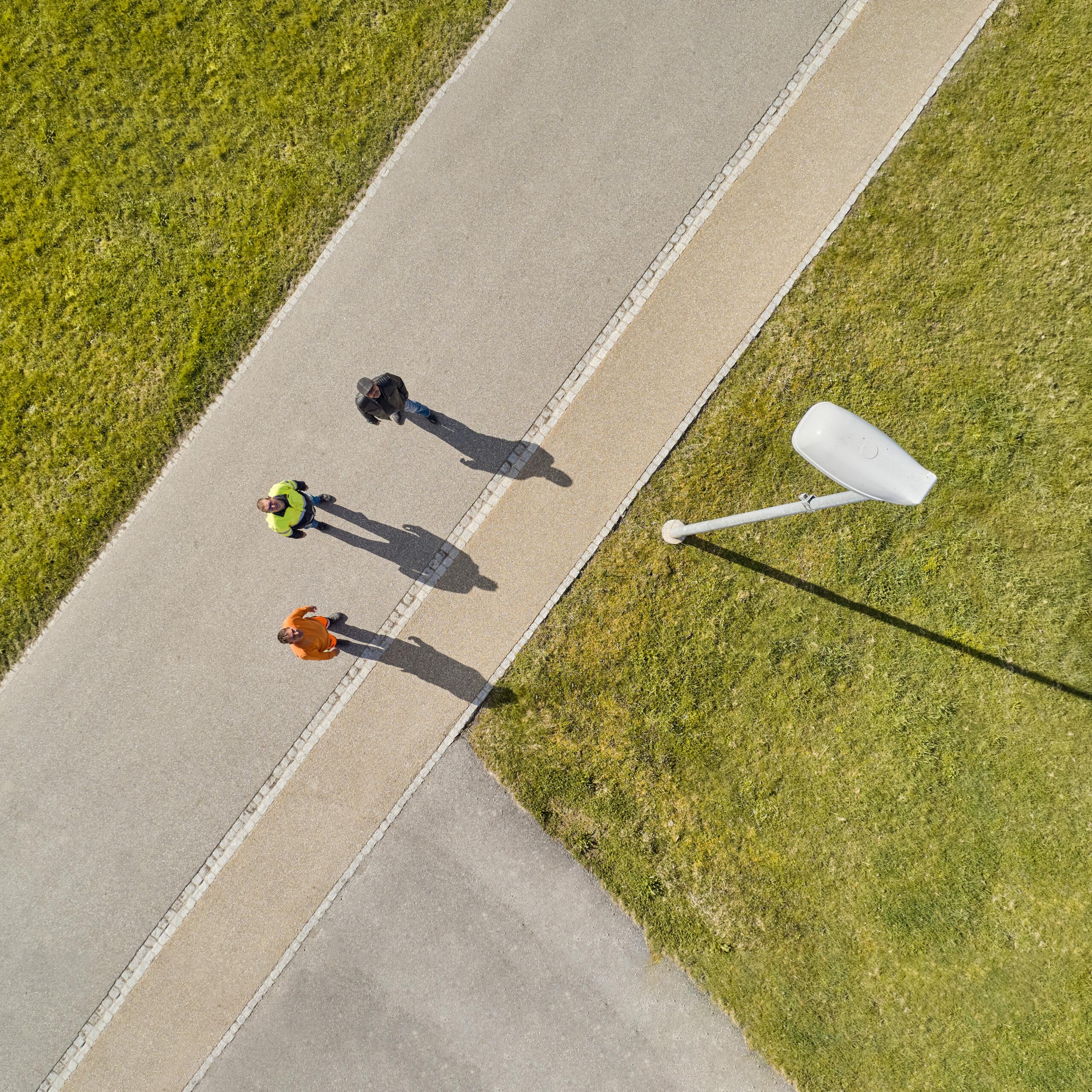 Michael Müller, Projektleiter Netze bei Elektra, steht mit zwei Gemeindemitarbeitenden auf der Strasse und schaut einem Kandelaber empor. Die Elektra bietet Gemeinden Dienstleistungen für die öffentliche Beleuchtung an.