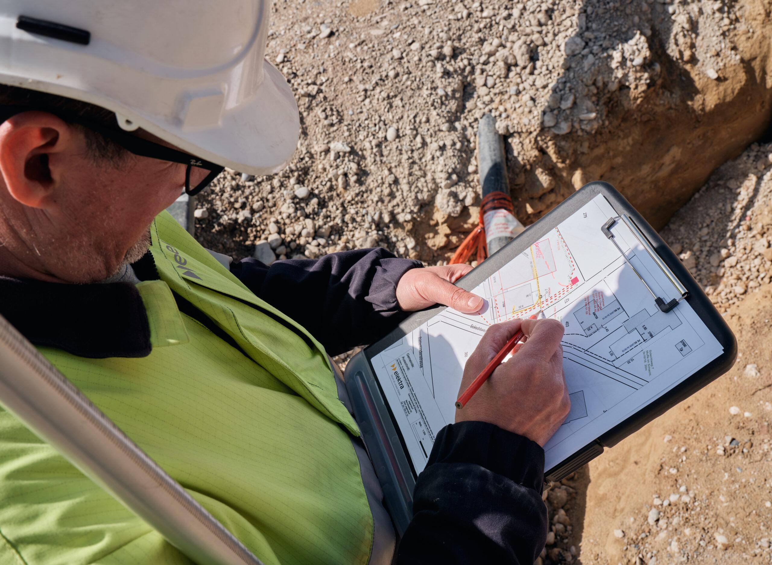 Michael Müller, Projektleiter Netze bei Elektra, ist auf der Baustelle und zeichnet eine Stromleitung auf einem Katasterplan ein.